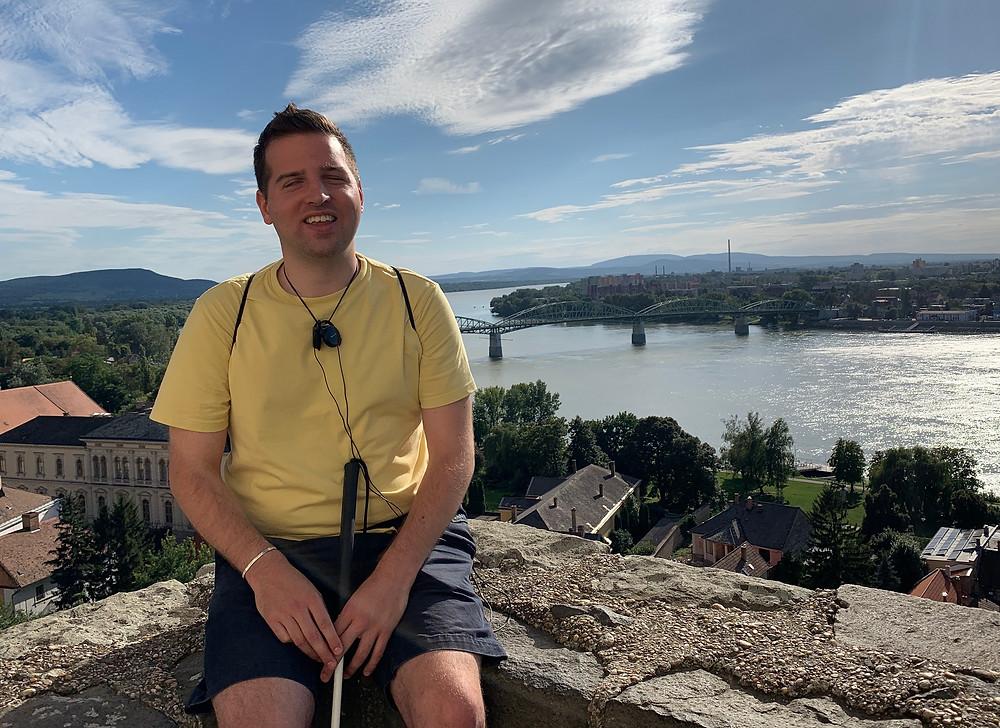 Juhász Tomi kirándul. Egy várfalon ül. Mögötte a Duna látszik.a látszik