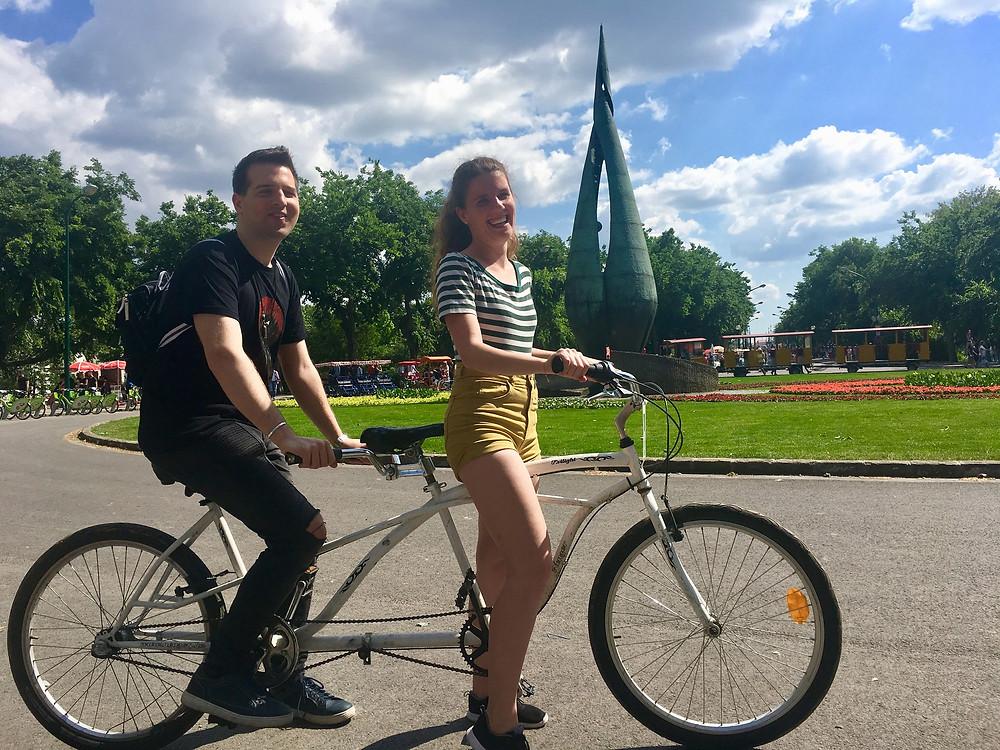 Tomi és Kitti együtt bicikliznek. Tandem biciklin ülnek. A tandem biciklin két ülés van egymás mögött. Kitt elöl vezet, Tomi hátul ül.