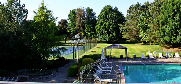 Swimming Pool and Tennis Courts with a lawn and trees in the background