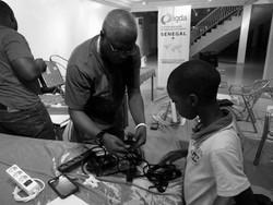 Père enseignant la technique de rangement de cables d'ordinateur à son fils , après une Lan party sur Call of Duty au Sénégal.