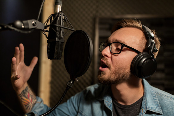 music, show business, people and voice concept - male singer with headphones and microphone singing song at sound recording studio.jpg
