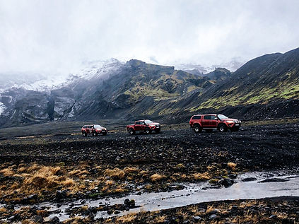 three toyota car riding in island mountains at the background