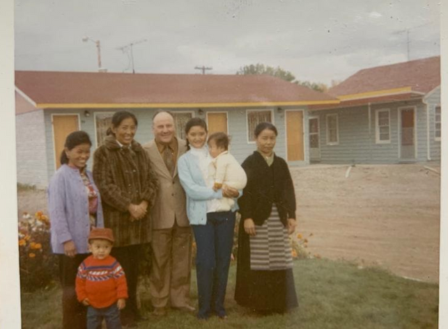 "Tibetans alongside Mike ""Manpower"" who helped resettle Tibetans in Alberta. Taken in front of a motel in which newly arrived Tibetans stayed (1971)."
