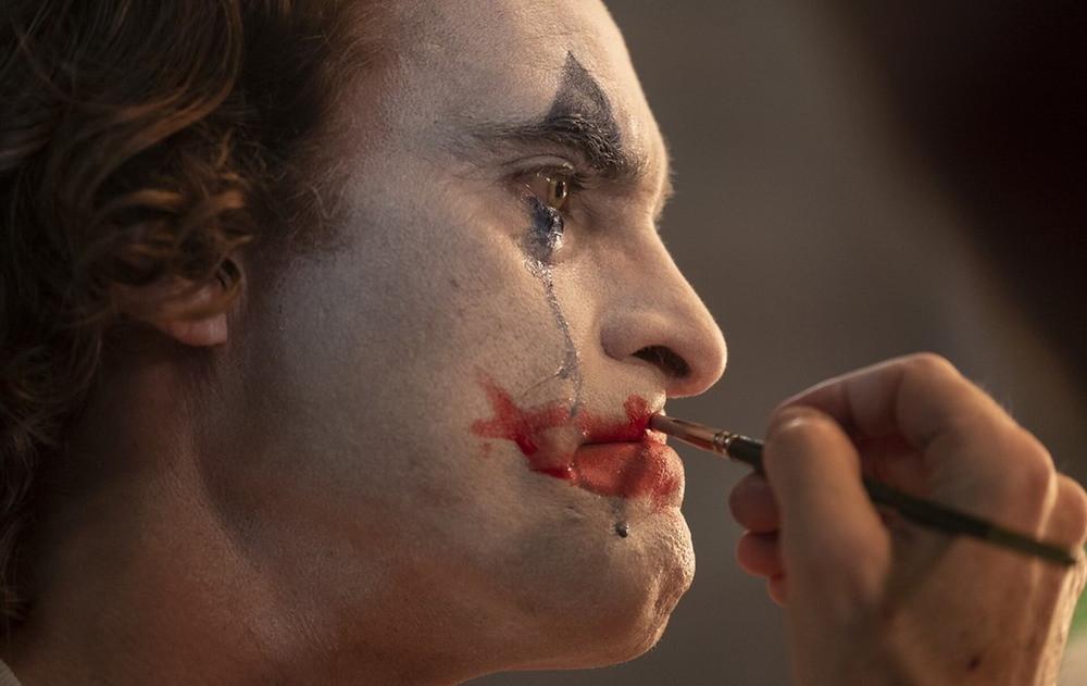 Joaquin Phoenix in 'Joker' (2019). The main character applies messy clown lipstick to his face. (Credit: Warner Bros)