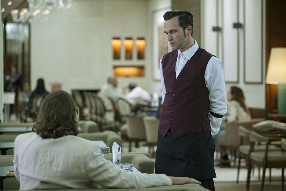 A still from the 2018 film, The Waiter, directed by Steve Krikris. The main character portrayed by Aris Servetalis talks to a long-haired man facing away from the camera in a restaurant. Aris' character is dressed as a waiter.