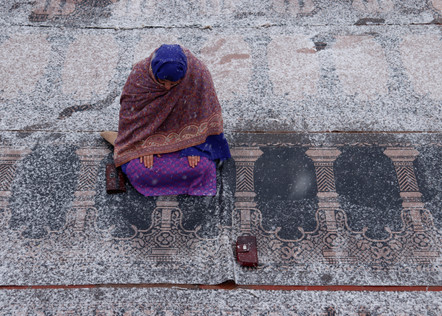 Photo: Zainab Mufti - A devotee offers prayers in Hazratbal Shrine whilst it snows.