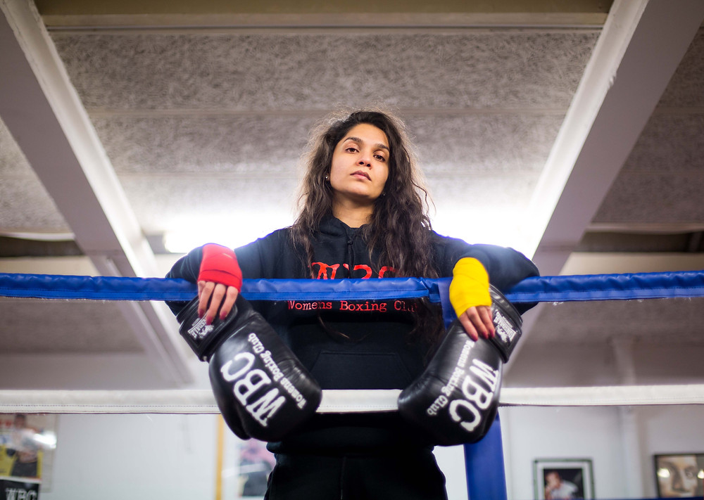 Photograph of a Muslim female boxer standing in a ring with boxing gloves. Photograph by Birmingham artist Anisa Fazal