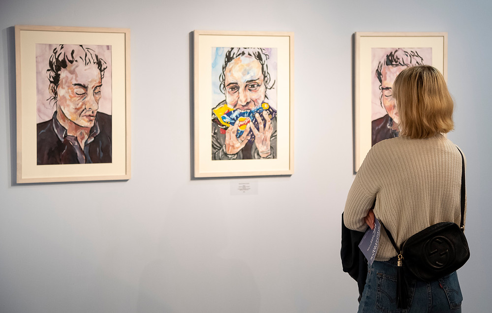 A woman looks at a triptych - three hand-illustrated portraits - on a blank wall in a gallery.