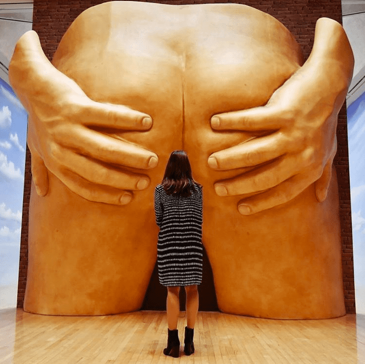 A photograph of Anthea Hamilton's 'Project For Door', a pair of giant spread buttcheeks in sculpture. In this photo, a woman is standing in front of the arsehole.