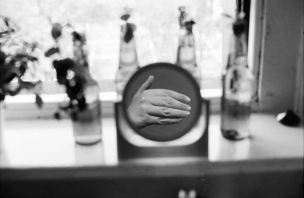 A monochrome photograph by Danish artist Mia Rewitz. The photograph is of a hand disembodied in a mirror against a window backdrop.