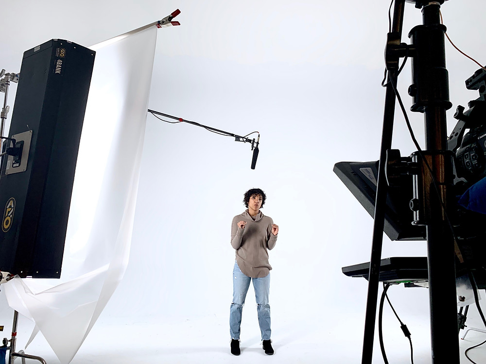 A woman stands in a white film studio speaking to a camera off-screen