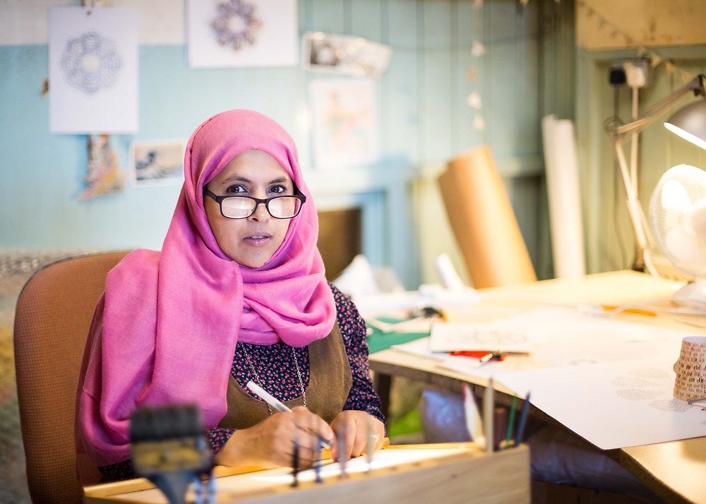 Anisa Fazal's ongoing photographic documentary series 'Beyond Belief'. This photo is of Birmingham artist Shaheen wearing a pink headdress and glasses holding a pen.