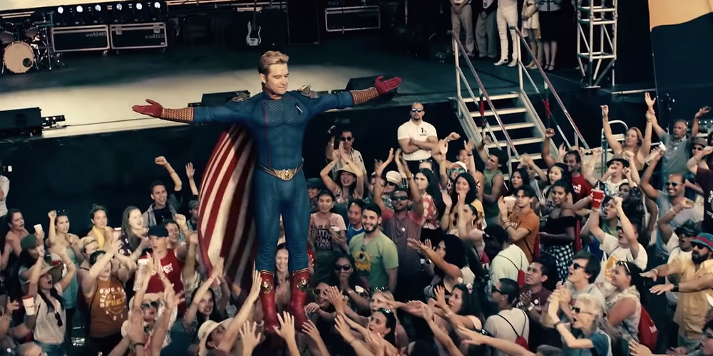A still from the Amazon Prime Original show, The Boys. A superhero stands above an adoring crowd.