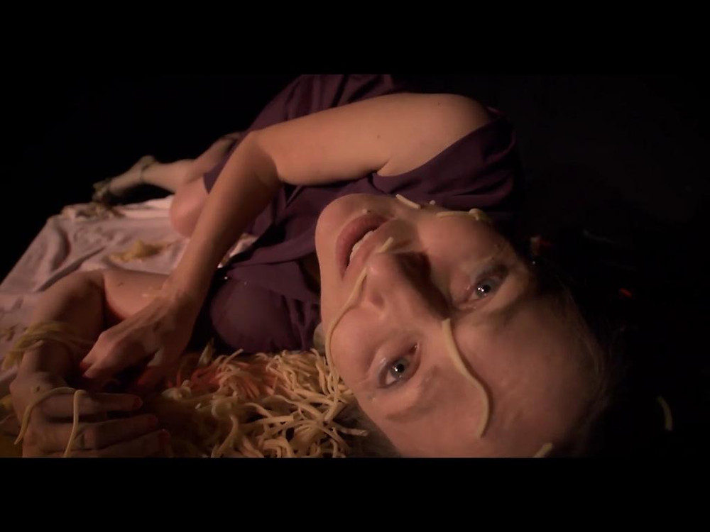 A still from the film Gelateria, directed by British-Italian Christian Serritiello. A woman laughs at the camera, covered in spaghetti.