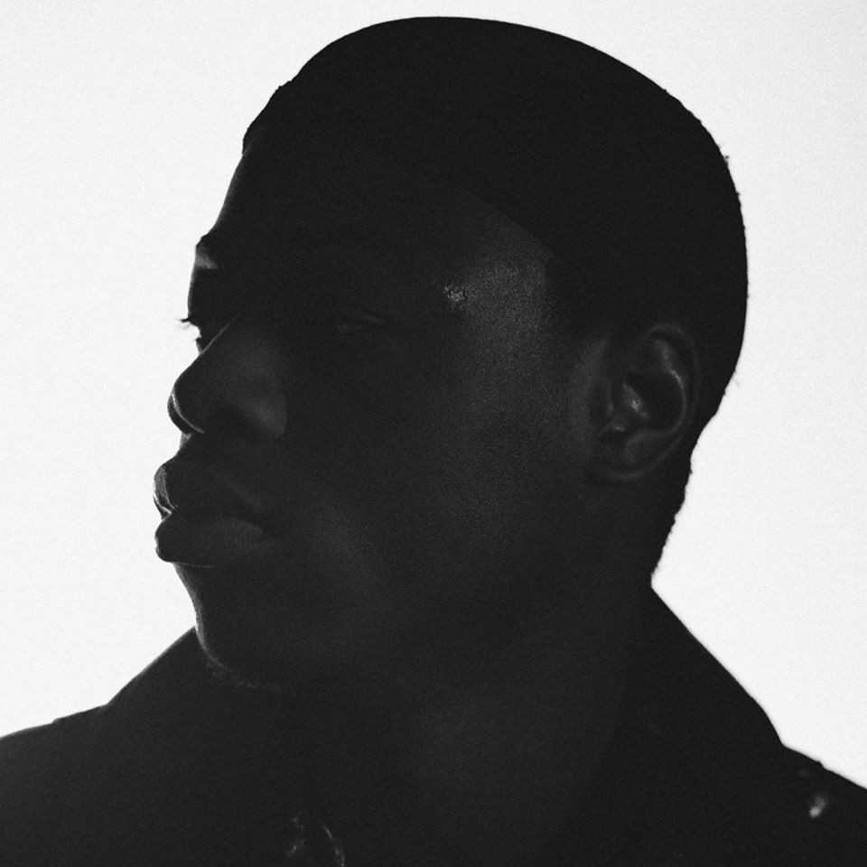 A photograph of J Hus, barely silhouetted against a white background. J Hus is a grime artist and rapper from London.