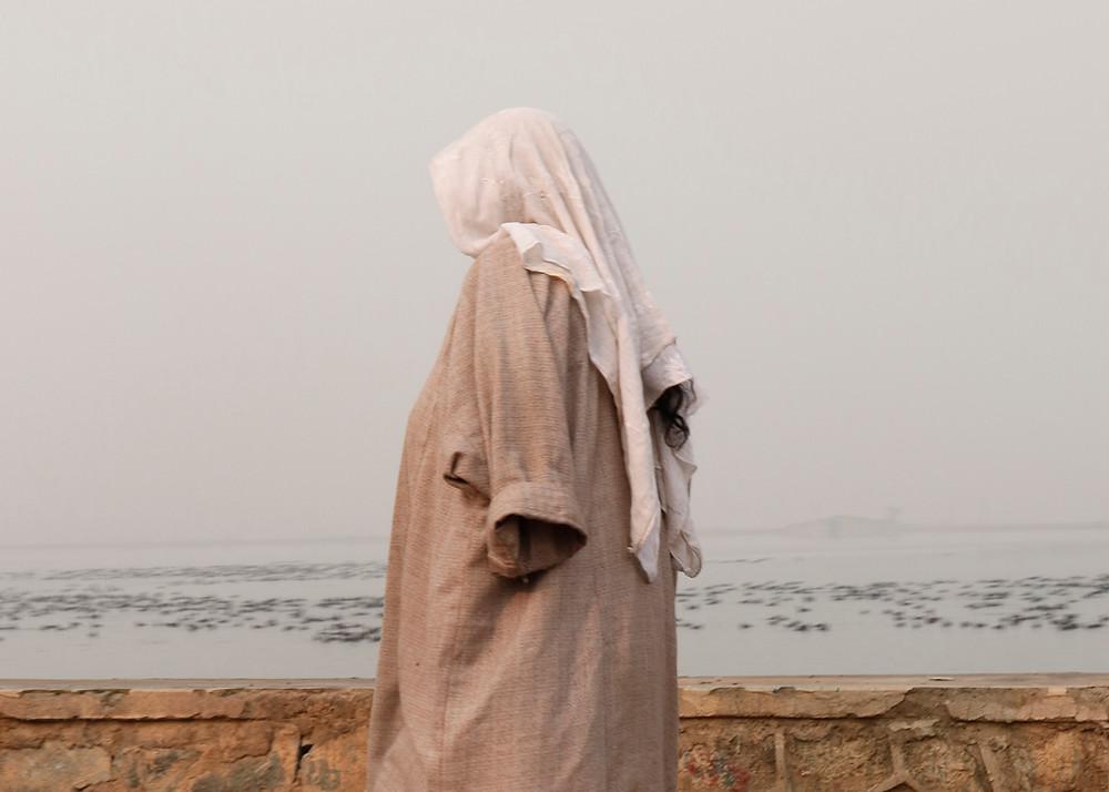 A Kashmiri woman walks on the banks of Dal Lake wearing a traditional attire. (Photo: Zainab Mufti)