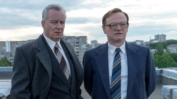 A still from the popular 2019 HBO series 'Chernobyl'. Two men in suits stand on a rooftop surveying the city of Pripyat, Ukraine.
