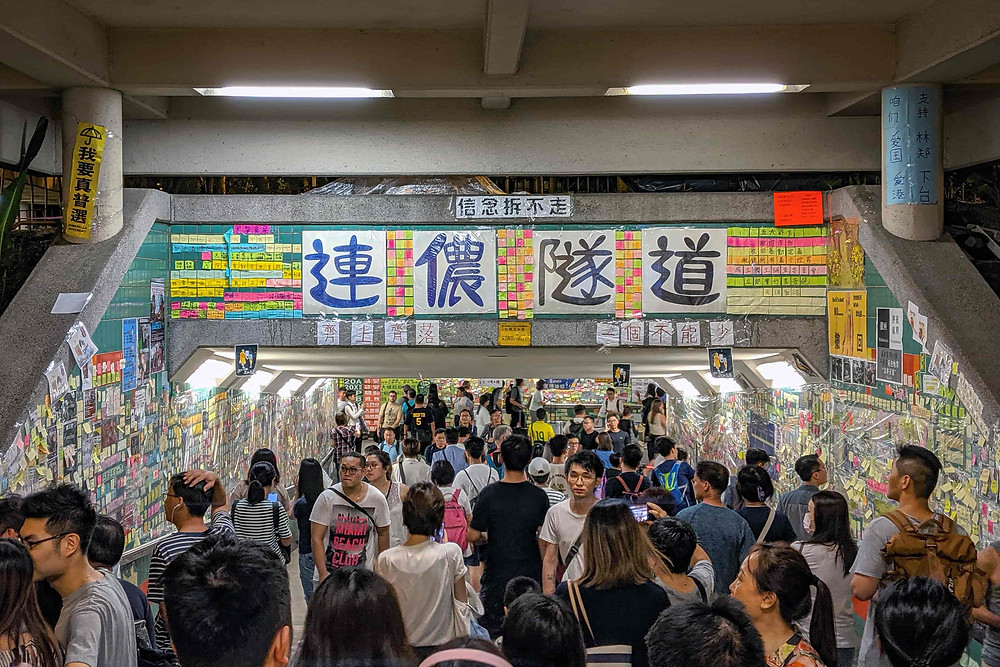 A photograph of the Tai Po Lennon Wall. A busy underpass is filled with people as well as fliers, posters, and banners.