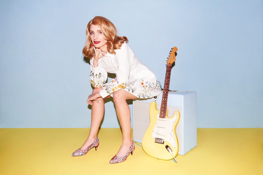 A photograph of Sadie Dupuis, the lead singer of band Speedy Ortiz. A woman is in a white dress sat on a guitar amp next to a yellow Fender Stratocaster.