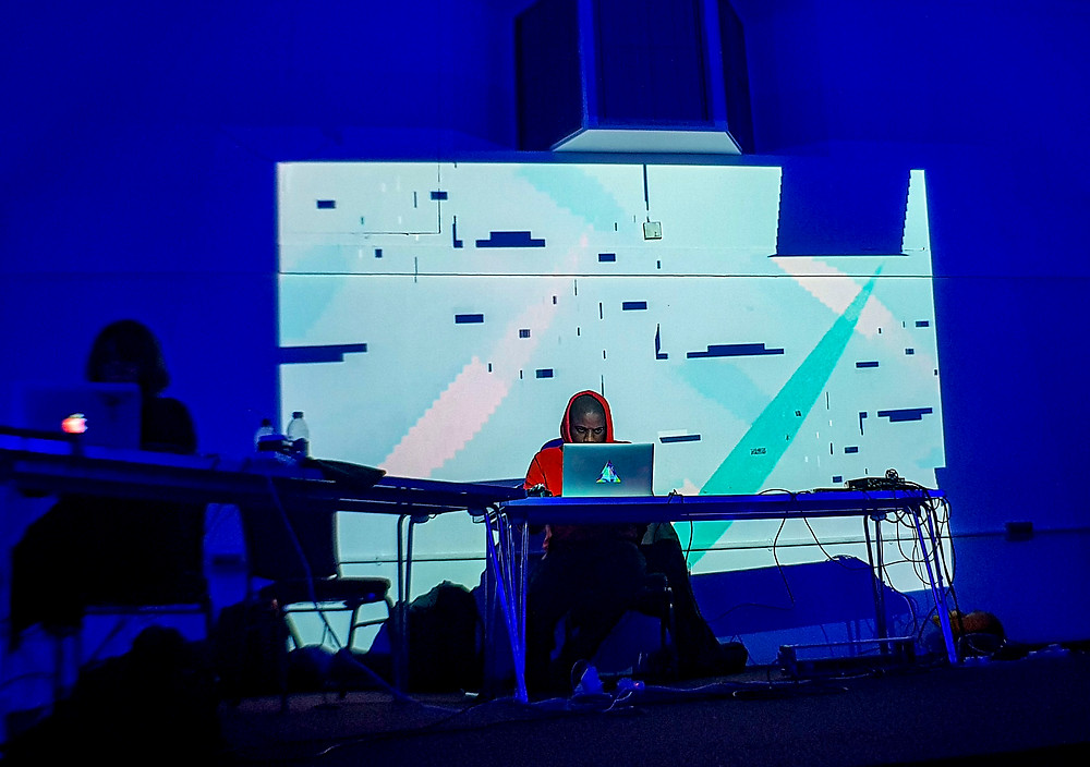 Algorave performers hellocatfood and a shadowy Joanne Armitage performing at Algowave in Waltham Forest Community Hub in London. Two DJs sat in front of laptops as a live trippy visual plays out on a projector behind them. (Photo: Ciaran Daly)