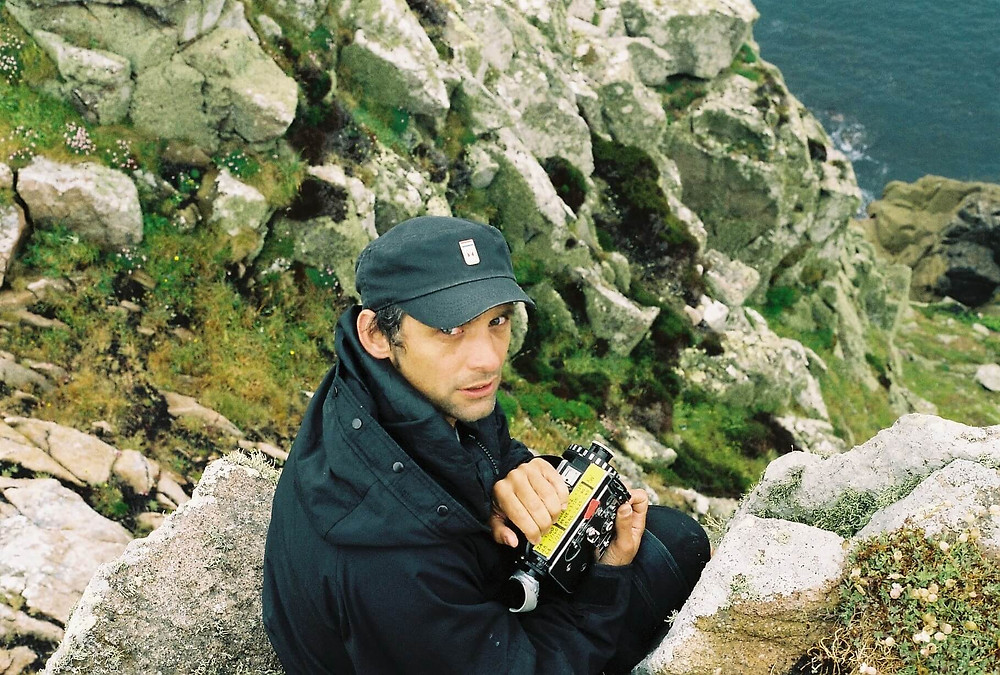 A photograph of 'Bait' director Mark Jenkin. He is sat on a clifftop holding an old analogue film camera. (Photo: Callum Mitchell)