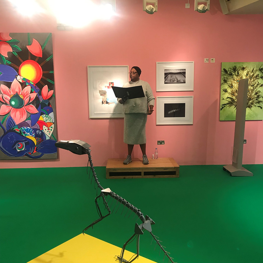 A woman reads from a book in an art gallery at a performance entitled 'Voices Out Loud'. There is a dinosaur skeleton sculpture in front of her.