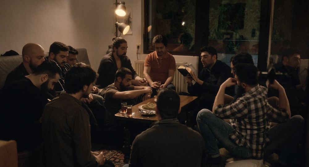 A still from 2019 film Oray, directed by Mehmet Akif Büyükatalay. A group of Muslim men sit around a table drinking tea and reading the Quran.