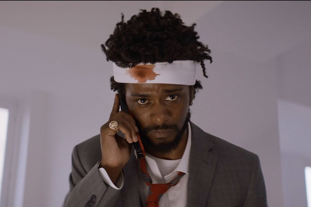 A still from the 2018 sci fi / fantasy film 'Sorry To Bother You'. The main character Lakeith Stanfield is on a mobile phone with a bandage round his head with a blood stain on it.