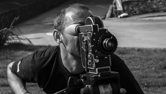 The director of 'Bait' (2019), Mark Jenkin, shooting the film on a 16mm camera. He is outside on grass. Monochrome shot.