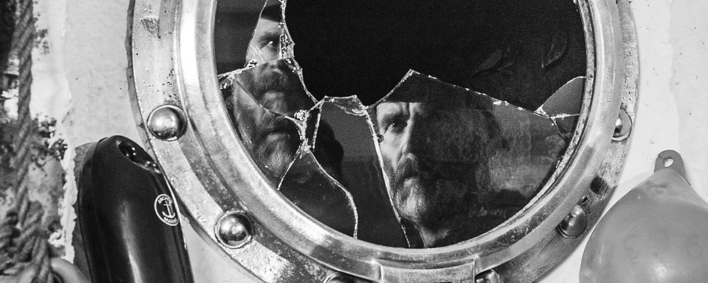A still from Mark Jenkin's 2019 film Bait. Monochrome shot of an old man with beard looking at his fragmented reflection in a broken mirror.