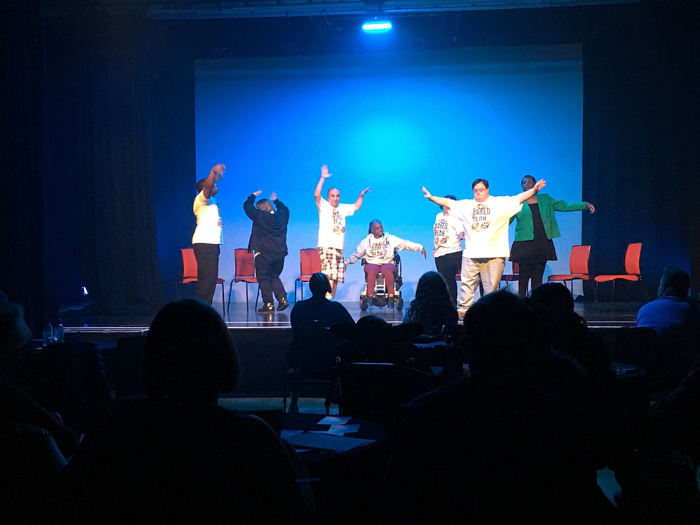 The Baked Bean Company onstage during their performance at the World Transformed in Brighton, September 2019. A group of actors with physical and learning disabilities raise their hands onstage during a play. (Photo: Baked Bean Company)