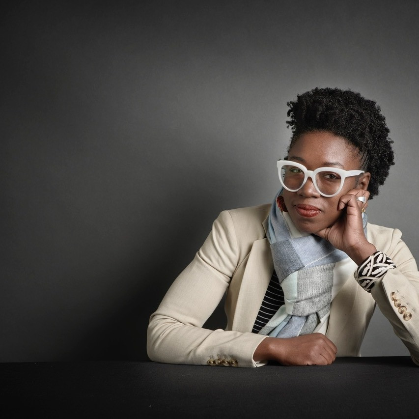 A photograph of Joy Buolamwini, a computer scientist and founder of the Algorithmic Justice League. Joy is wearing white glasses and a cream blazer, looking into the camera.