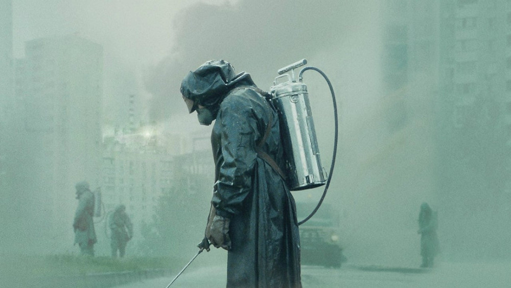 A still from the 2019 HBO series, 'Chernobyl'. Someone in a Hazmat suit is cleaning radiation in a foggy green cityscape.