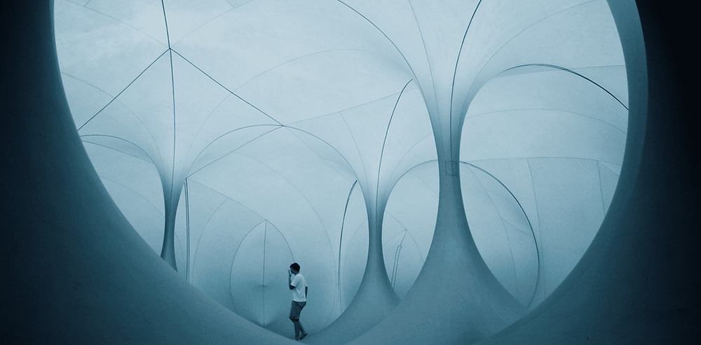 A still from the 2020 film 'The Reason I Jump'. A boy walks through a monochrome curved hallway space.