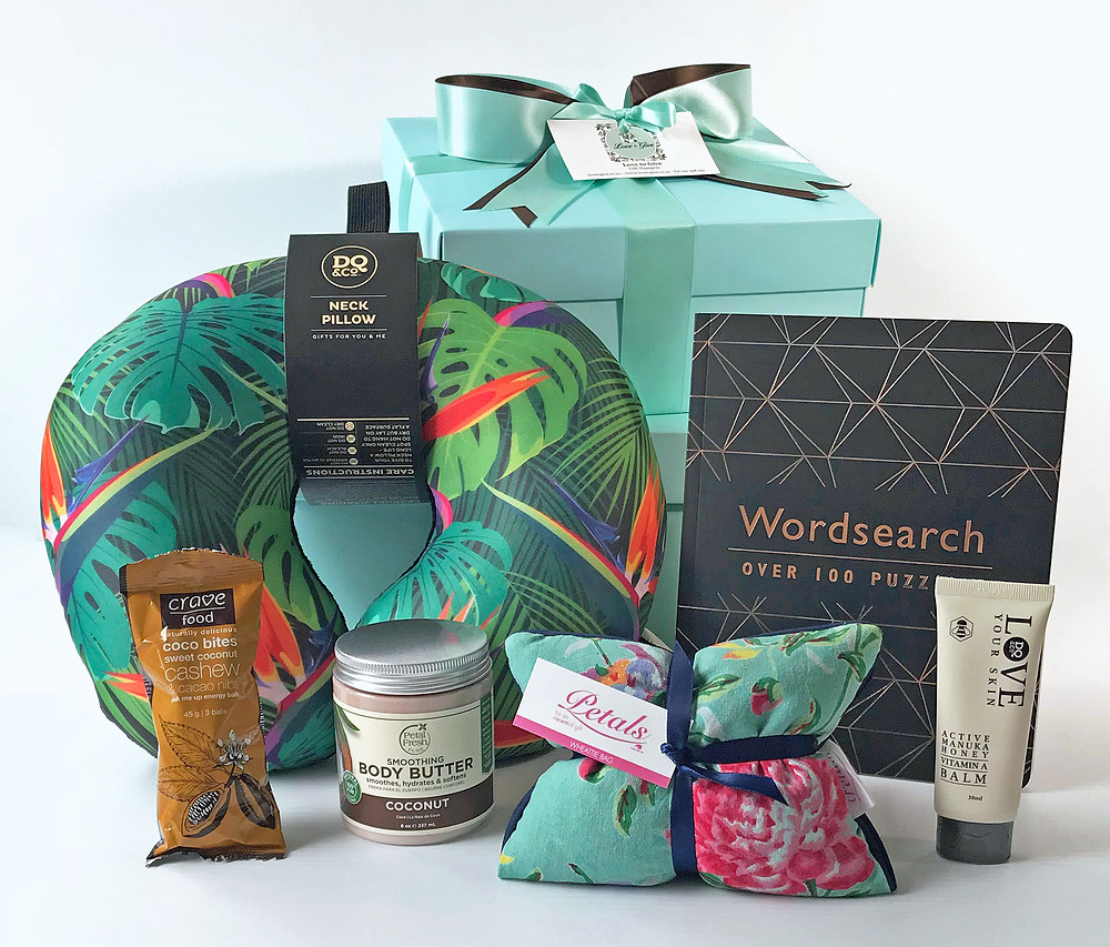 gift hamper containing; relaxing wheattie bag, healing balm, body lotion, word-search puzzle book, neck pillow, energy snack
