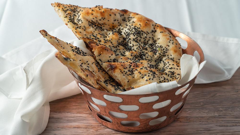 """נאן - זו הגרסה המאורכת והמועשרת של הצ'פאטי. הלחם עבה יותר ודומה בצורתו ללאפה או לפיתה עיראקית. בד""""כ אוכלים את הנאן עם  עם חמאה או גבינה"""