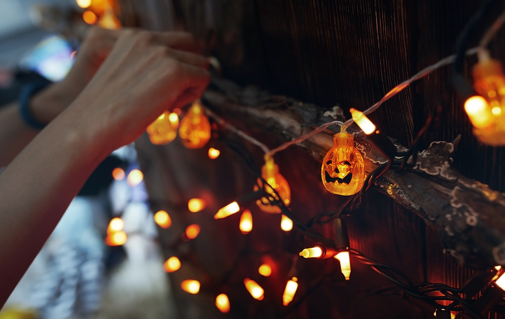A pair of hands string up a set of orange, pumpkin shaped lights. Photograph courtesy of Wix.