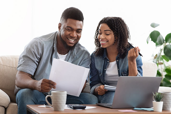 Happy black couple reading financial documentation at home while planning family budget to