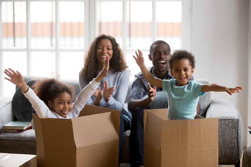 Happy african american parents and kids playing in boxes enjoy relocation into new home, e...dad.jpg
