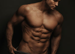 Male fitness model standing on black bac