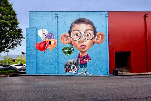 """1º mural: Como todos os outros personagens """"Big Ears"""", este remete ações do mundoinfanto-juvenil. Neste é o menino já com espinhas e um curativo para esconde-las (masno caso chamando mais atenção). Em uma ação passeando com seu cão e tomandorefrigerante. Os balões possibilitam o publico a interagir com a arte.  First Wall:  just like all the other """"Big Ears"""" characters this wall refers to thejuvenile and kids' world. This one is of a boy that has pimples and is using aband-aid to hide some of it. My intention was to use the bandage to attractmore attention to the piece. The boy is walking with his dog and drinkingsoda. I also added balloons to allow people to interact with the art."""