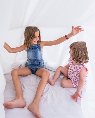 Sisters Playing in White Sheets on Bed