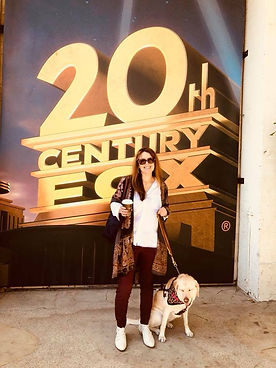 Kristin stands in front of a 20th Century Fox sign. She holds coffee in one hand and Zoe's leash in the other, and Zoe sits by her feet wearing a leopard print bandana.