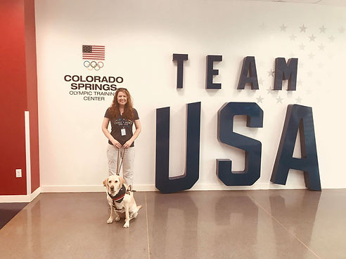Kristin stands in front of team USA sign at the Olympic Trainig Center in Colorado Sprigs. Zoe sits at her feet wearing a patriotic bandana