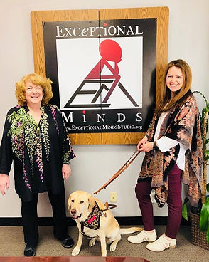 Kristin and a woman from Exceptioal Minds stand in front of an Exceptional Minds sign with Zoe sitting in between them.