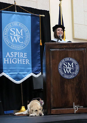 Kristin stands behind the podium on stage, speaking at the graduation of Saint Mary-Of-The-Woods in Indina. Zoe lays next to the podium.