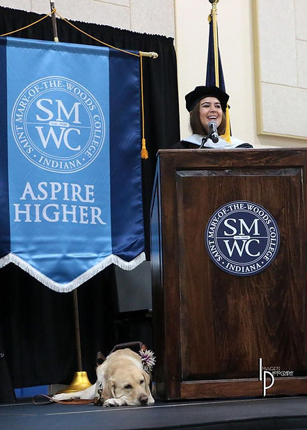 Kristin speaks at the gradiation of Saint Mary-Of-The-Woods College in Indiana. Zoe, her seeing eye dog, lays at her feet next to the podium.