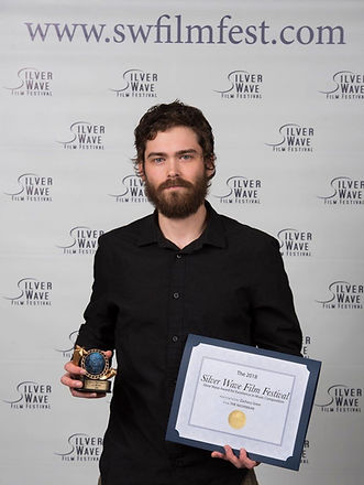 Zachary Greer receives the Excellence in Music Composition award at Silver Wave Film Festival (2018).