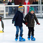 two-children-inside-of-ice-skating-field