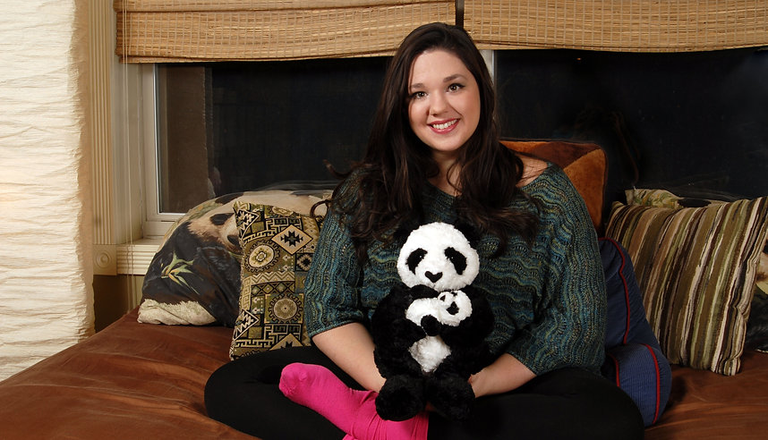 Woma sitting on couch crossed legged with panda in lap smiling